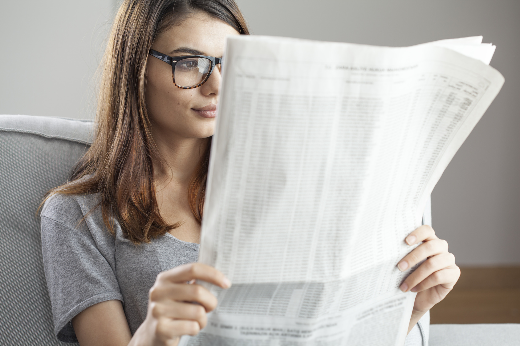 Fotolia_123889625_Young-woman-reading-newspaper_M