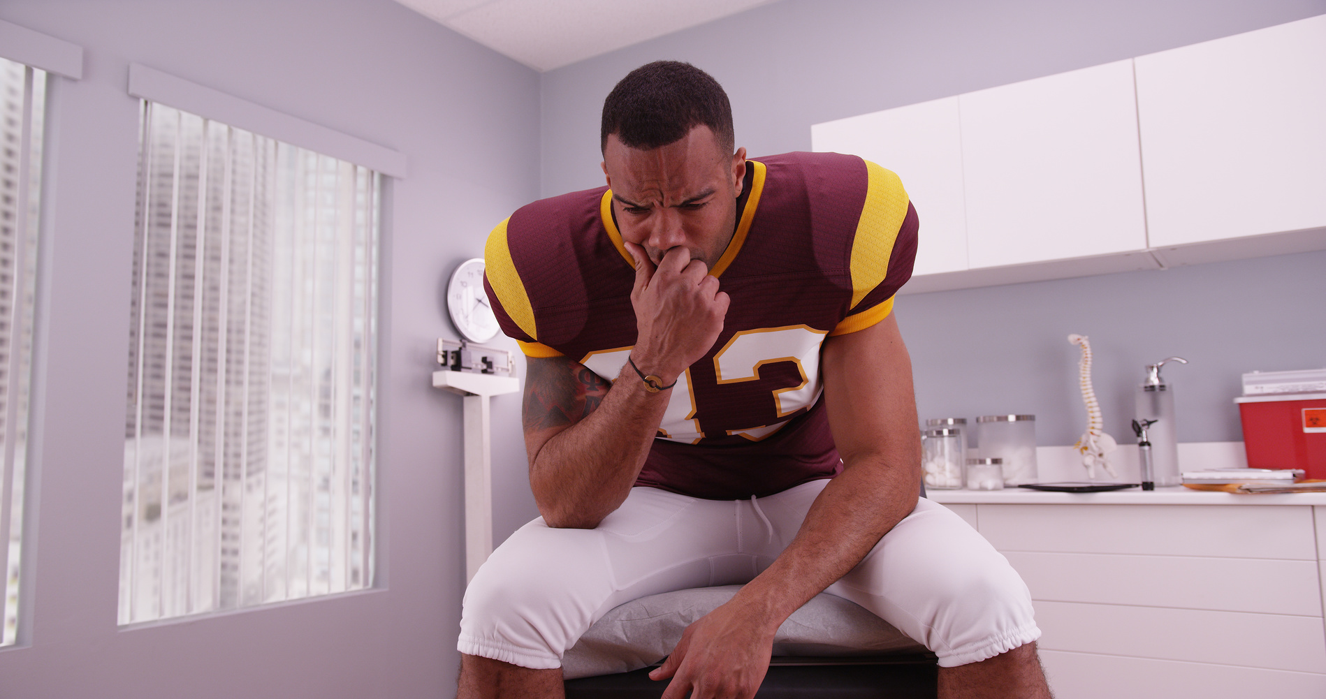 Fotolia_104436129_Football-Player-at-Doctors-Office_M