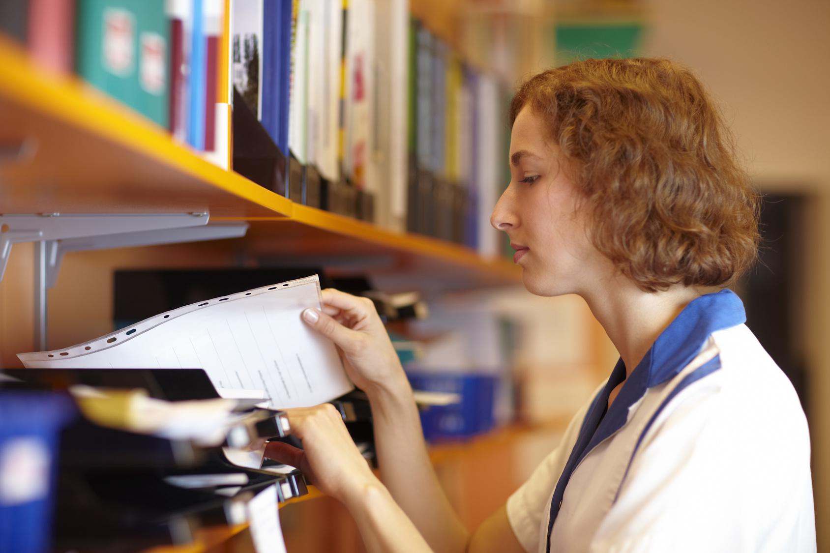 Fotolia_18989010_woman looking at files_M