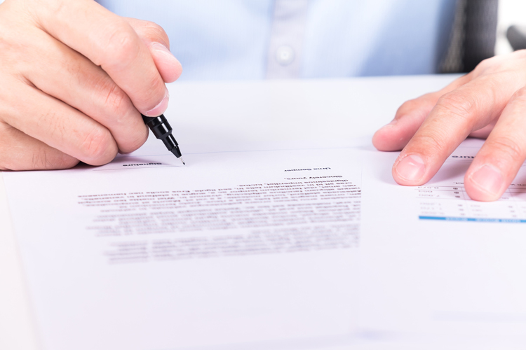 businessman's hand signing a document on desk