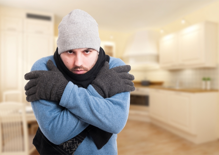 man shivering in house