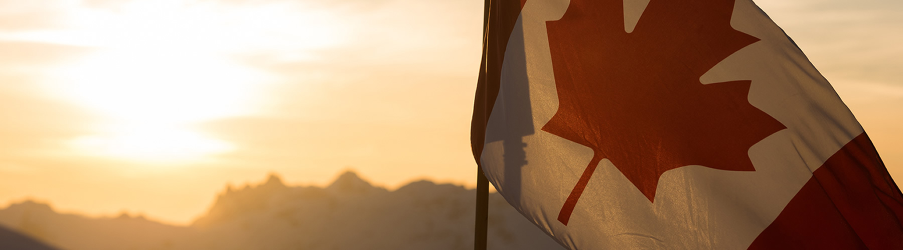Canadian flag in the mountains at sunset